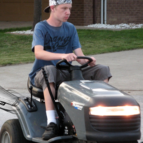 Older Trysten riding a lawn mower
